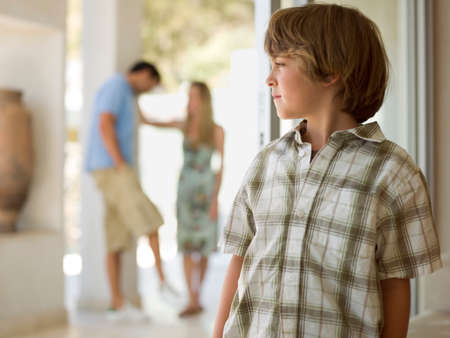 checkered polo shirt: A boy standing,parents in the background LANG_EVOIMAGES