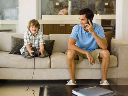 checkered polo shirt: Boy playing video game,father on the phone