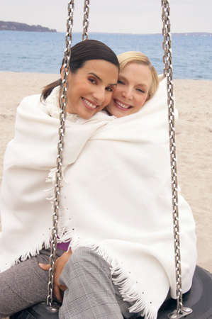 female bonding: Portrait of two young women sitting on a tire swing and wrapped in a shawl LANG_EVOIMAGES