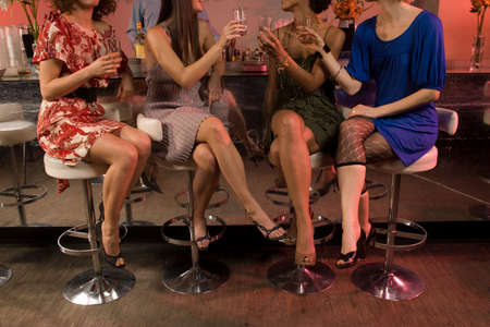 legs crossed on knee: Women drinking at a bar