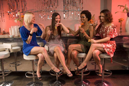 legs crossed at knee: Women drinking at a bar