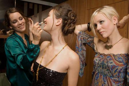 make public: Women applying make up