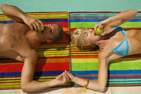 two piece swimsuits: Couple lying down beside the pool LANG_EVOIMAGES