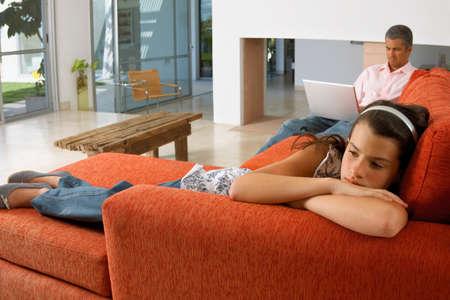 girl lying down: Muchacha que se acuesta en un sof�, padre trabajando en la computadora port�til