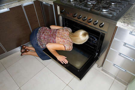 kneeling: A woman kneeling down to look at an oven