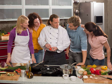 teaching adult: Male Chef teaching four students in the kitchen