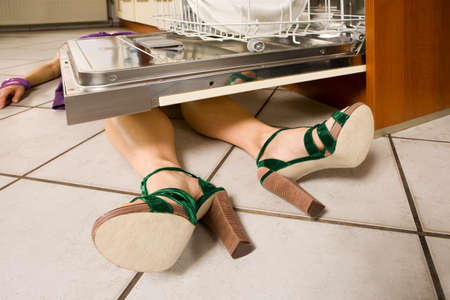 life and death: Woman lying under a dishwasher