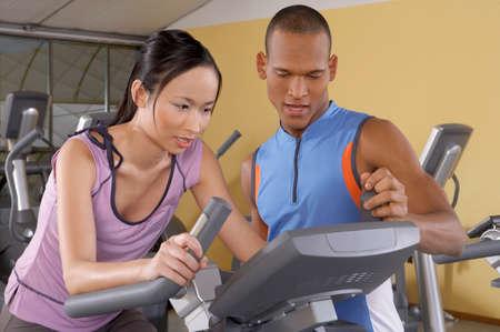 aide à la personne: Formateur aider une femme avec le cycle dans un gymnase LANG_EVOIMAGES