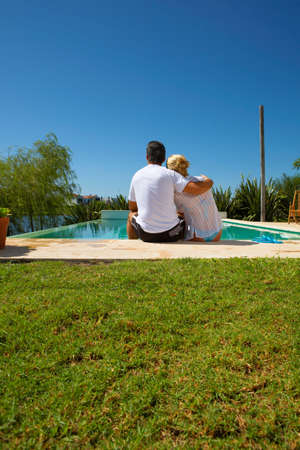 low blouse: A couple sitting by the pool