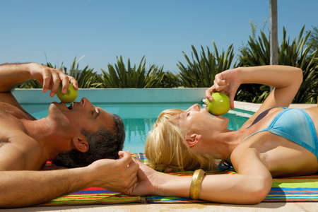 two piece swimsuit: Couple lying down beside the pool LANG_EVOIMAGES