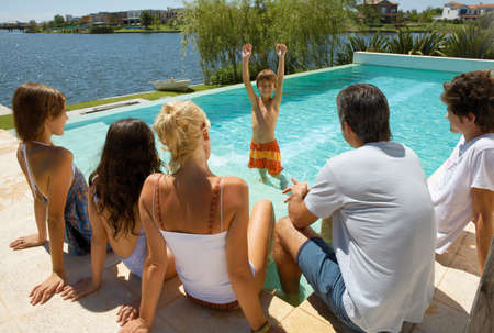 swimming costumes: Family relaxing by the pool