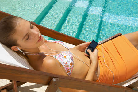 one teenager: Girl listening to her music player.