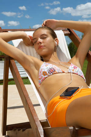 two piece swimsuits: Girl listening to her music player.