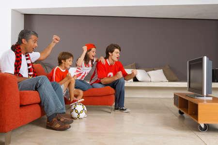 mujer viendo tv: Viendo un partido de deportes en la televisi�n Familia