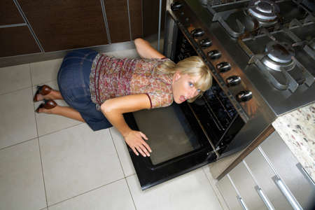 donna in ginocchio: A woman kneeling down to look at an oven
