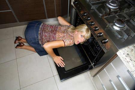 mujer arrodillada: Una mujer de rodillas para mirar un horno