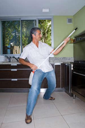 air guitar: Man playing air guitar with mop LANG_EVOIMAGES