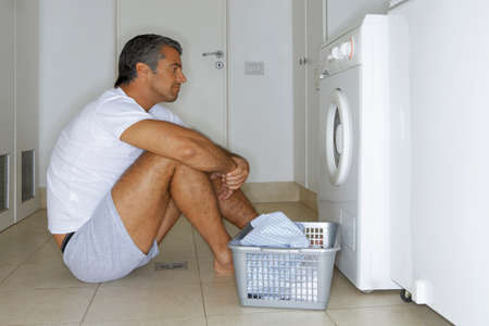 tidiness: Man sitting in front of a washing machine