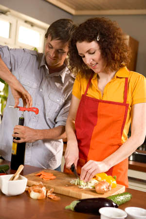 cutting vegetables: Woman cutting vegetables,man opening wine