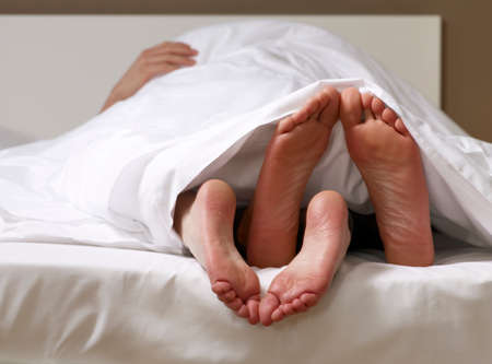 adult foot: Young couple in bed