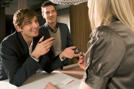 only three people: Two businessmen talking to a receptionist