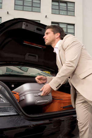 car trunk: Man taking a luggage from a car trunk