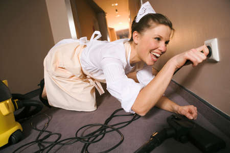 plugging: Close-up of a maid plugging in the cable of a vacuum cleaner LANG_EVOIMAGES