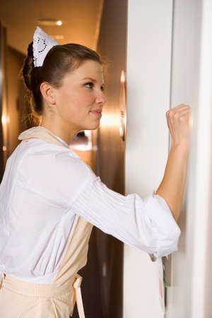 knocking: Side profile of a maid knocking at a door