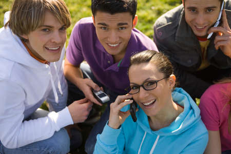 flip phone: A young woman talking on a mobile phone with her friends smiling around her
