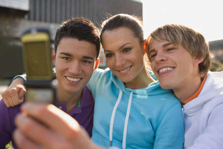flip phone: A young woman and two young men looking at a mobile phone and smiling LANG_EVOIMAGES