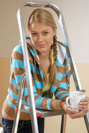 step ladder: Portrait of a young woman leaning on a step ladder and holding a coffee cup