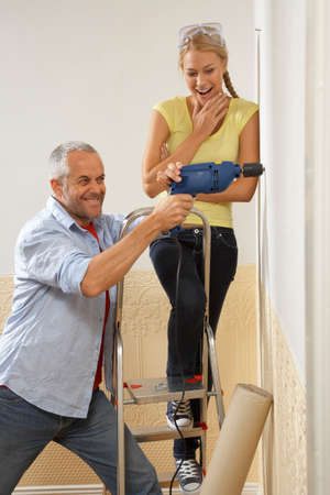 step ladder: Mid adult man drilling into a wall with a young woman standing on a step ladder