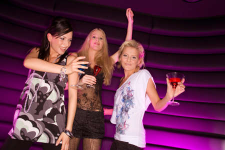 female bonding: Low angle view of three young women dancing in a nightclub LANG_EVOIMAGES