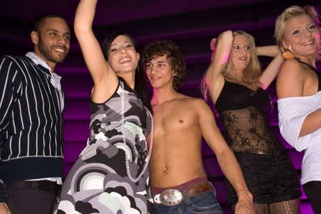 gente bailando: Cinco personas bailando en un club nocturno