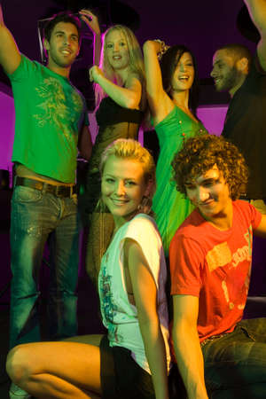 squatting down: Group of people dancing in a nightclub LANG_EVOIMAGES
