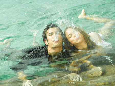 two people only: High angle view of a young couple spitting water in the sea