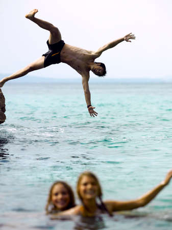 swimming shorts: Two young women in the sea with a young man jumping behind them