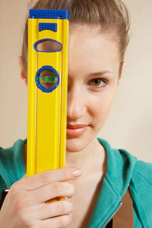 spirit level: Portrait of a young woman holding a spirit level LANG_EVOIMAGES