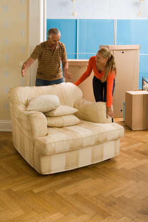 cardboard only: Couple adjusting an armchair and smiling