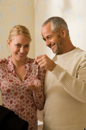 mid adult man: Mediados de hombre adulto que da una clave para una mujer joven LANG_EVOIMAGES