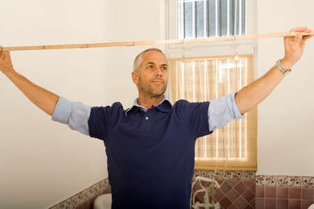 rolled up sleeves: Mid adult man measuring a wall with a tape measure