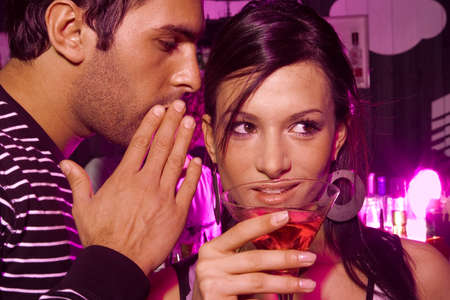 two persons only: Man whispering into a young womans ear in a bar