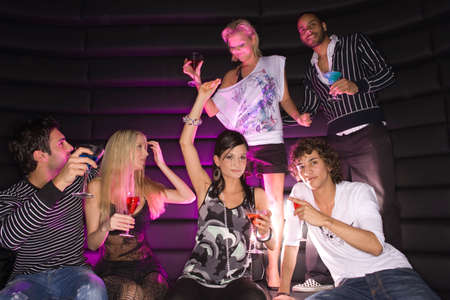 six persons: Young couple dancing in a nightclub with their friends having drinks