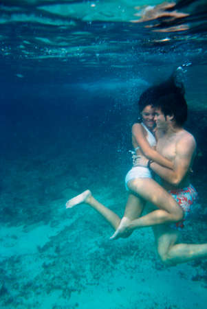mid adult couple: A mid adult couple swimming underwater