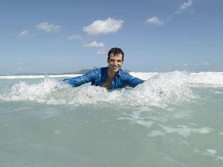 waist deep: A man splashing water in the sea