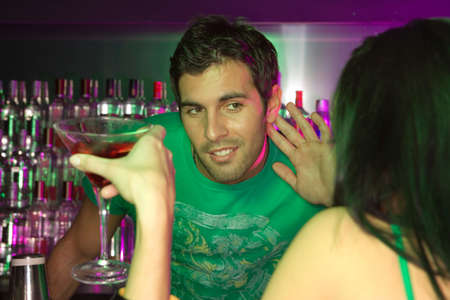 only three people: Bartender trying to listen to woman at bar counter