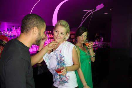 bar counter: Three people at a bar counter LANG_EVOIMAGES