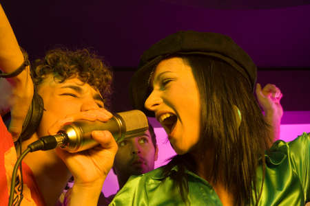 karaoke: Close-up of a young couple singing in a nightclub