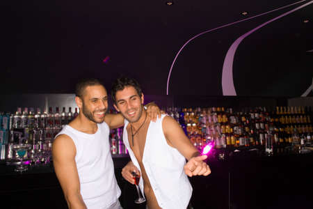 male bonding: Two young men standing in a nightclub and smiling LANG_EVOIMAGES