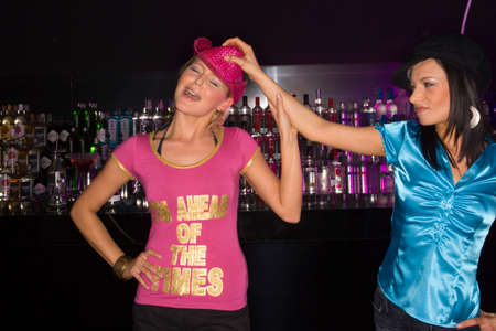 female bonding: Young woman taking a womans hat off in a nightclub